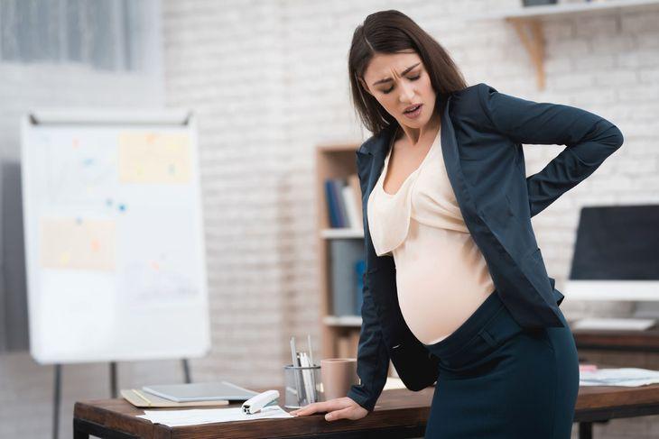 Беременная женщина опираеться на стол