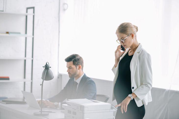 Беременная девушка разговаривает по телефону в офисе рядом с сотрудником