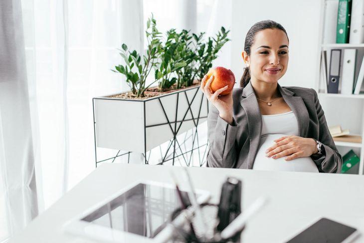 Беременная женщина держит в руке яблоко