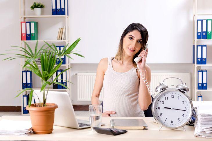Беременная девушка говорит по телефону