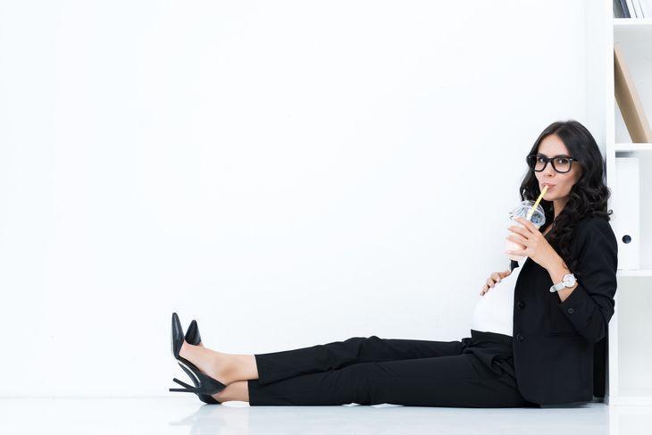 Беременная женщина потягивает напиток через трубочку