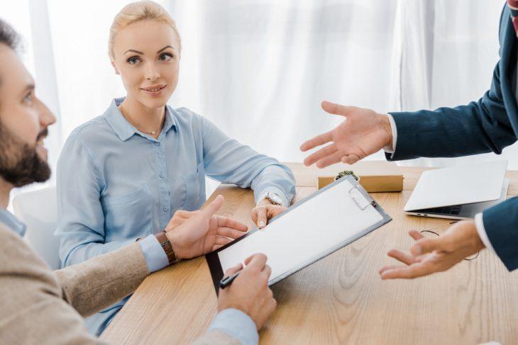Мужчины и женщина за столом ведут обсуждение