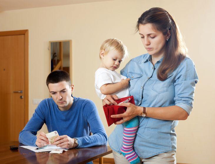 Молодая семейная пара с ребенком пересчитывает деньги