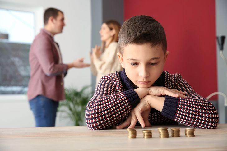 пока супруги что-то обсуждают ребенок за столом рассматривает монеты