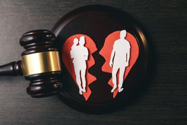 Разделенная семья в разделенном сердце лежит на подставке для молотка судьи