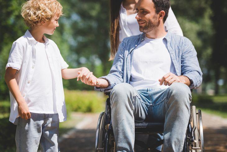 Молодой отец в инвалидной коляске общается с сыном