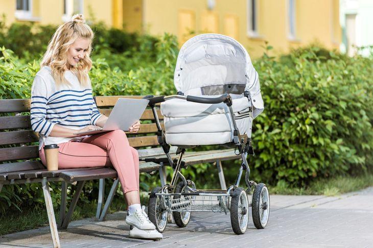 Женщина с коляской и ноутбуком сидит на скамейке