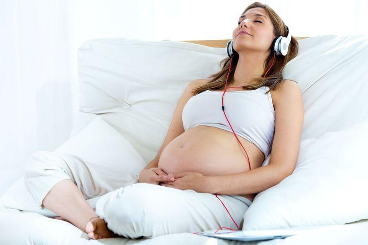 беременная девушка слушает музыку
