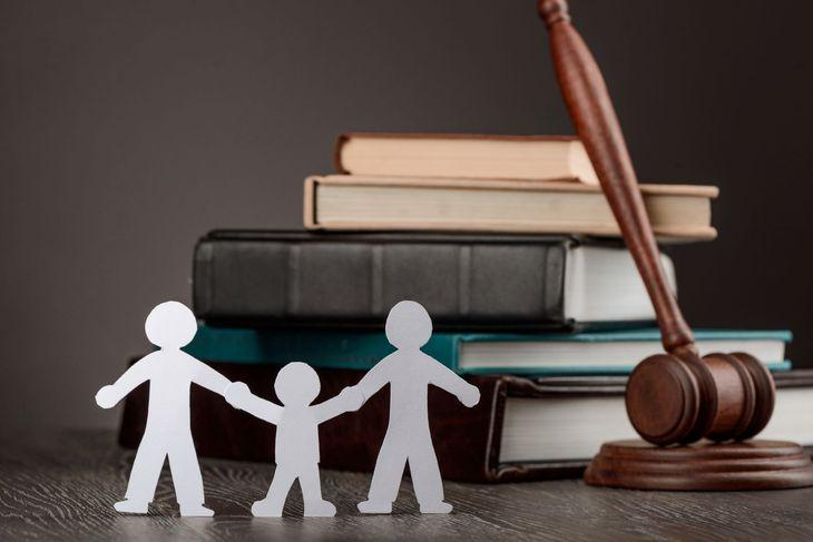 Семья вырезанная из бумаги стоит на столе рядом с книгами и молотком судьи