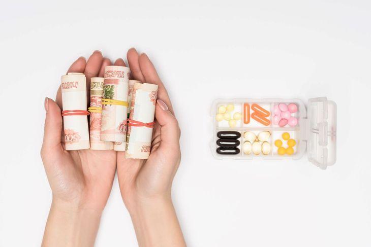 Руки держат свертки денег, а рядом лежат лекарства