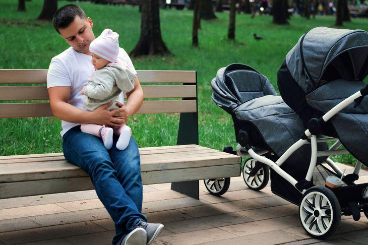 Папа с ребенком сидит на скамейке