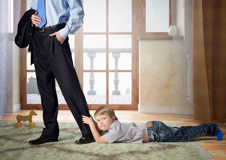Ребенок держится за ногу отца
