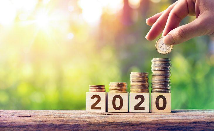 Стопки монет стоят на кубиках 2020