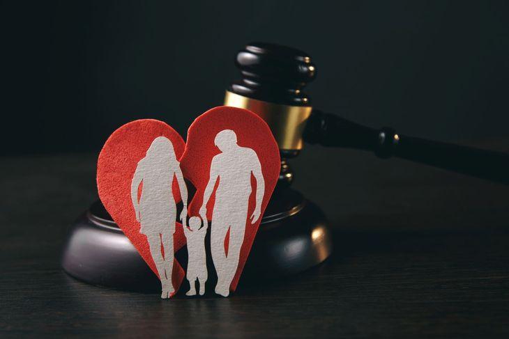 Разорванное сердце с семьей стоит оперевшись на молоток судьи