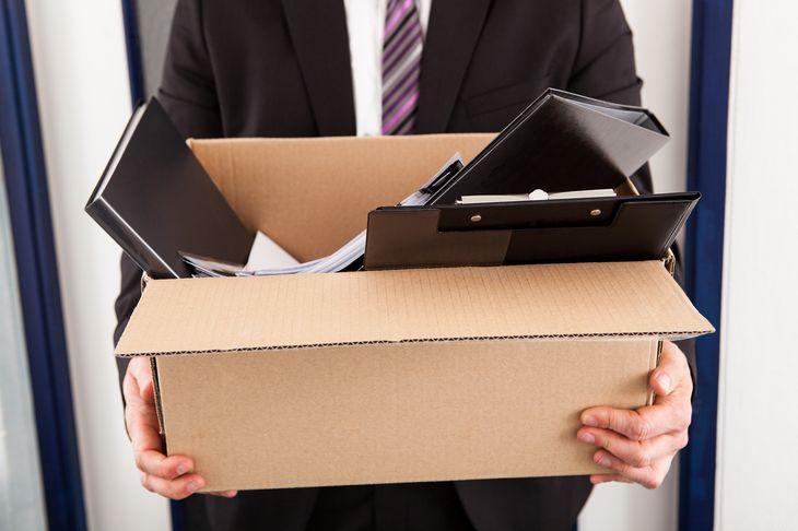 Мужчина держит коробку с документами