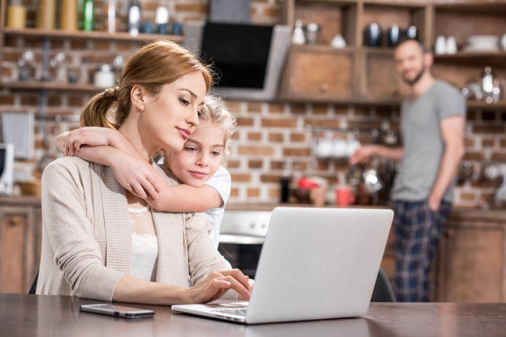 Мама обнимается с дочерью на кухне и на них смотрит отец ребёнка